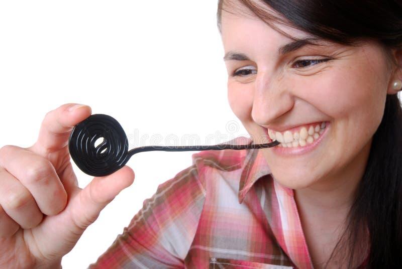 La donna mangia una rotella della caramella della liquirizia fotografie stock