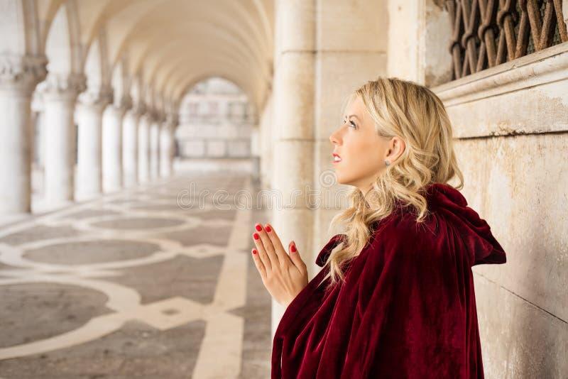 La donna in mantello rosso prega immagine stock libera da diritti