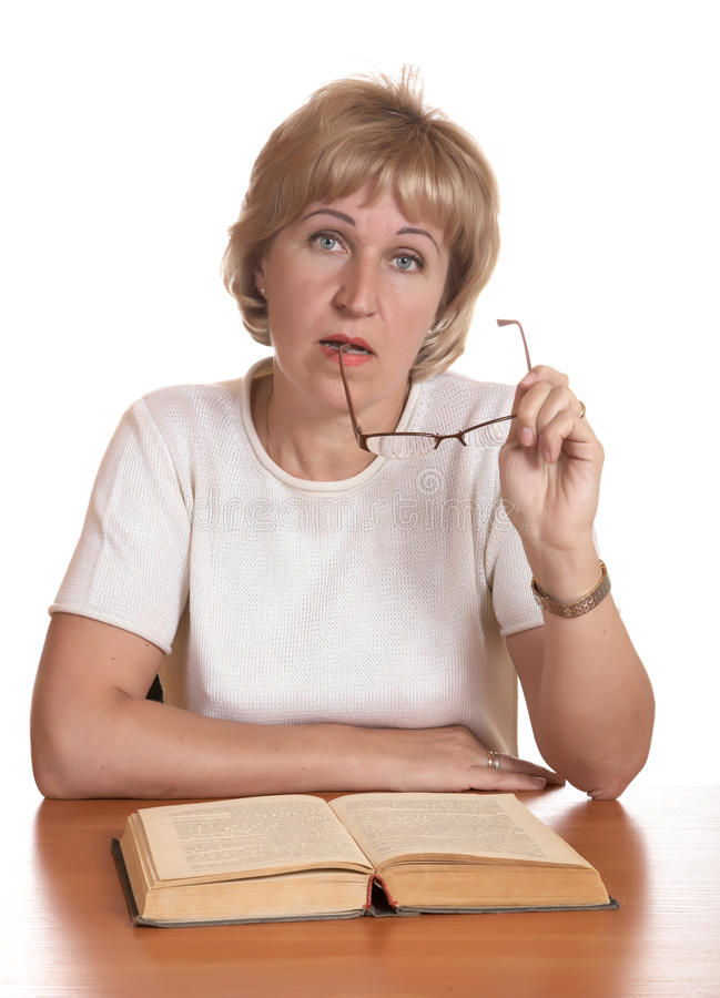 La donna matura con il libro dietro una tabella immagini stock