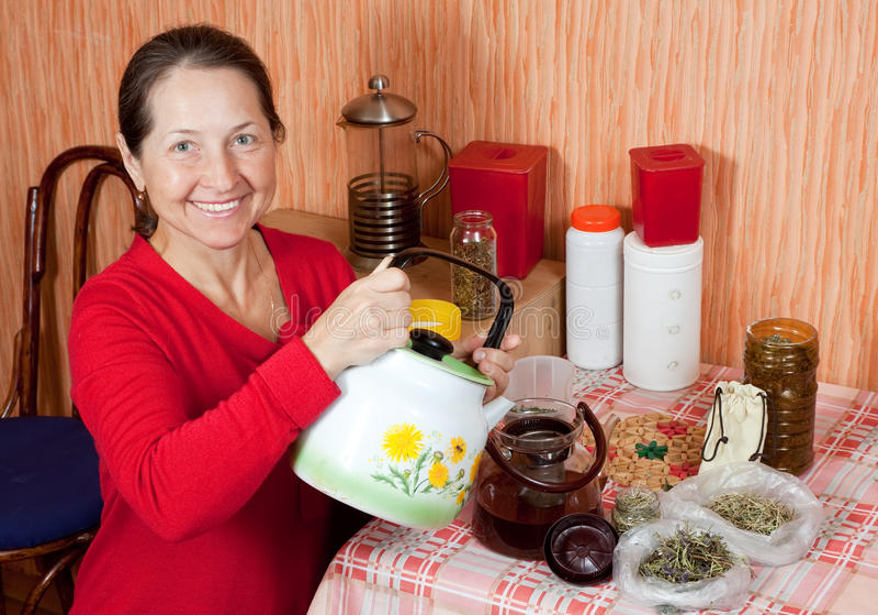 La donna matura fermenta le erbe fotografia stock