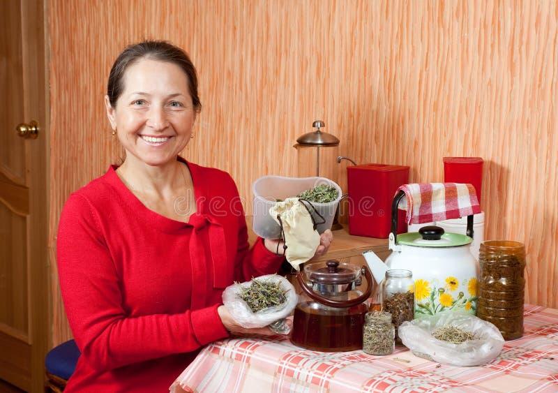 La donna matura fermenta le erbe immagini stock