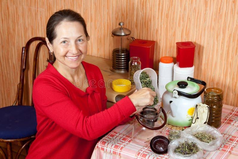 La donna matura fermenta le erbe immagine stock
