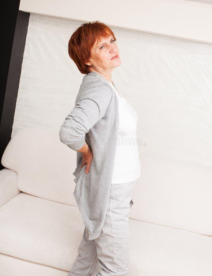 La donna matura ha parte posteriore di dolore dentro immagini stock libere da diritti