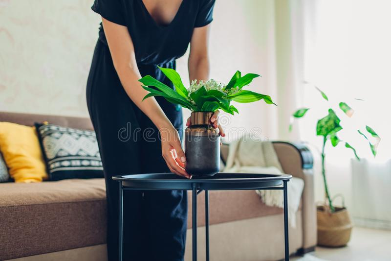 La donna mette il vaso con i fiori sulla tavola Casalinga che prende cura di comodit? in appartamento Interno e decorazione immagine stock libera da diritti