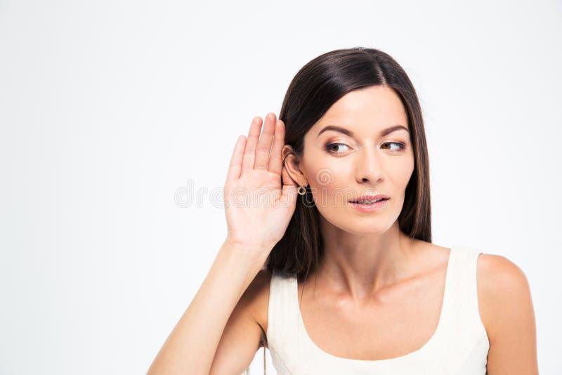 La donna mette una mano all'orecchio immagini stock