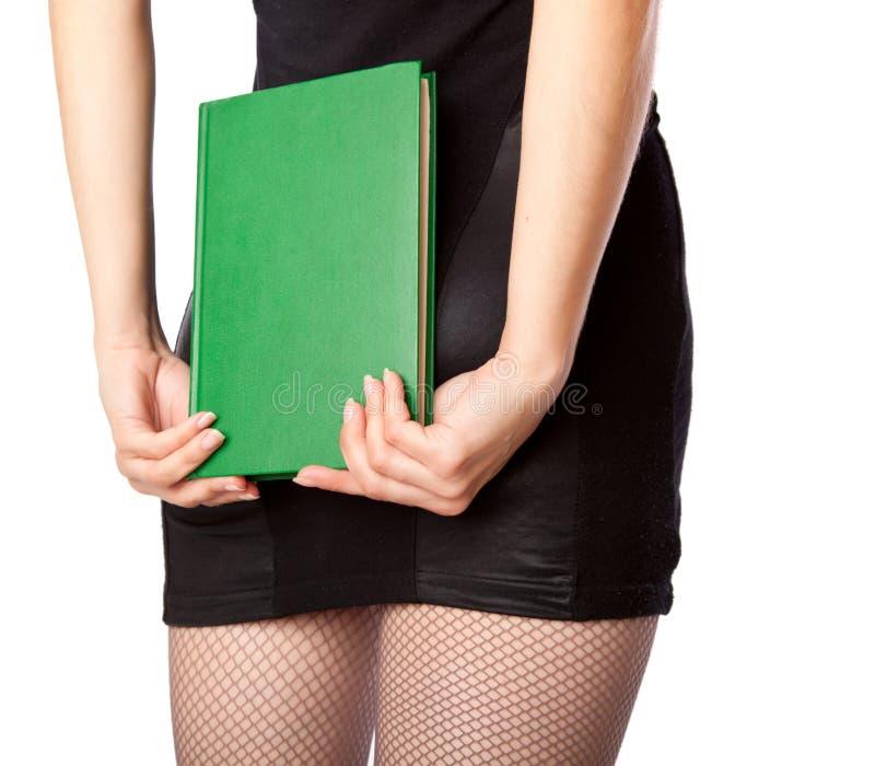 La donna in miniskirt sta tenendo il libro immagini stock libere da diritti