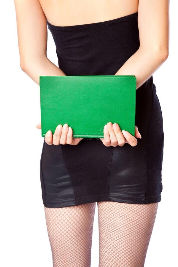 La donna in miniskirt sta tenendo il libro fotografia stock libera da diritti
