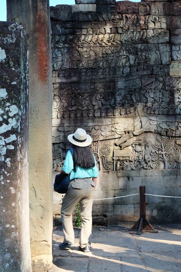 La donna mora in un cappello bianco esamina un bassorilievo antico Donna con capelli grigi in suoi capelli Turista fra il medieva fotografie stock libere da diritti