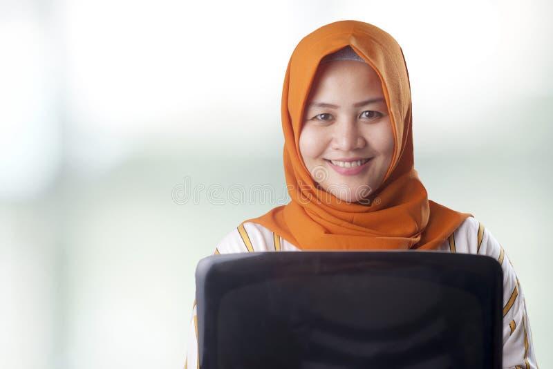 La donna musulmana tiene il computer portatile fotografie stock