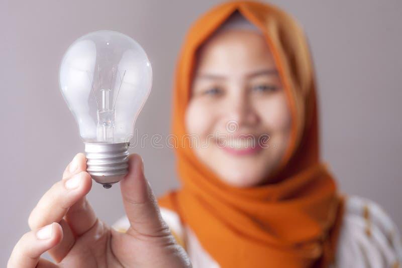 La donna musulmana tiene la lampadina fotografie stock