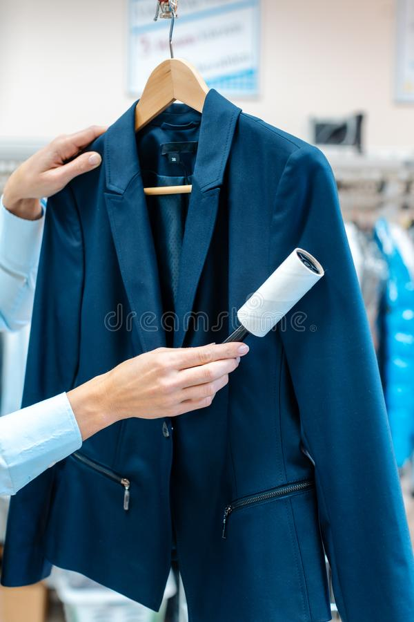La donna nel deposito di lavaggio a secco sta utilizzando il rullo del residuo di stoffa per pulire un rivestimento fotografia stock libera da diritti