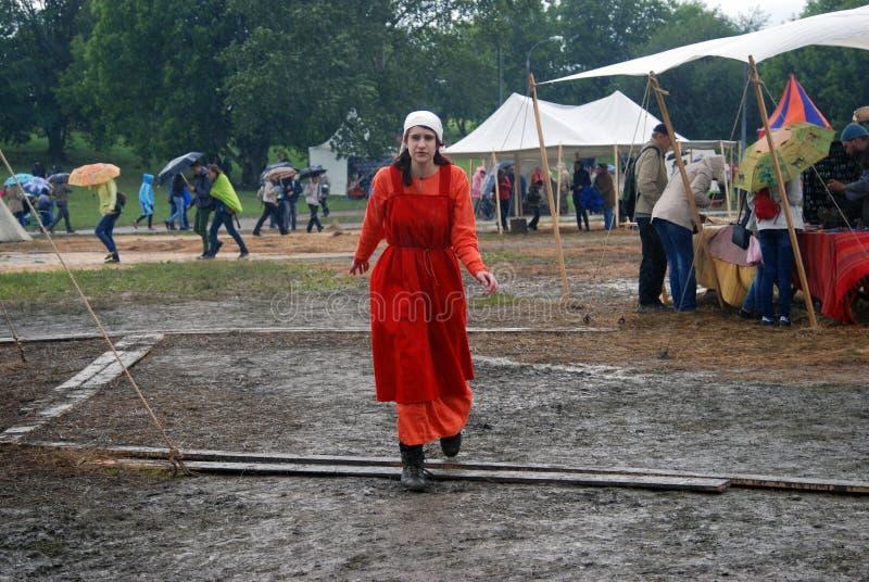 La donna nel rosso cammina sotto la pioggia senza ombrello immagini stock