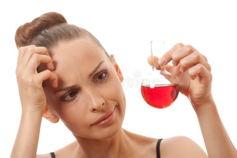 La donna nel vestito di sport tiene la boccetta con liquido rosso fotografia stock