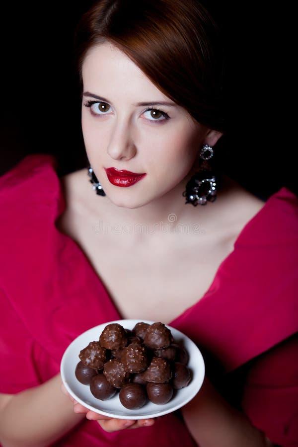 La donna nell'epoca vittoriana rossa copre con la caramella di cioccolato immagine stock
