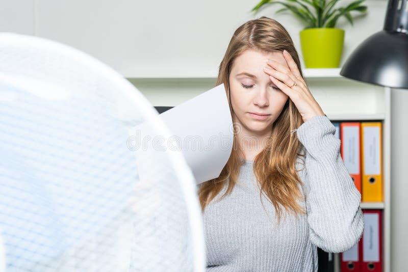 La donna nell'ufficio soffre dal calore e dal per mezzo di un ventilatore per raffreddamento fotografie stock