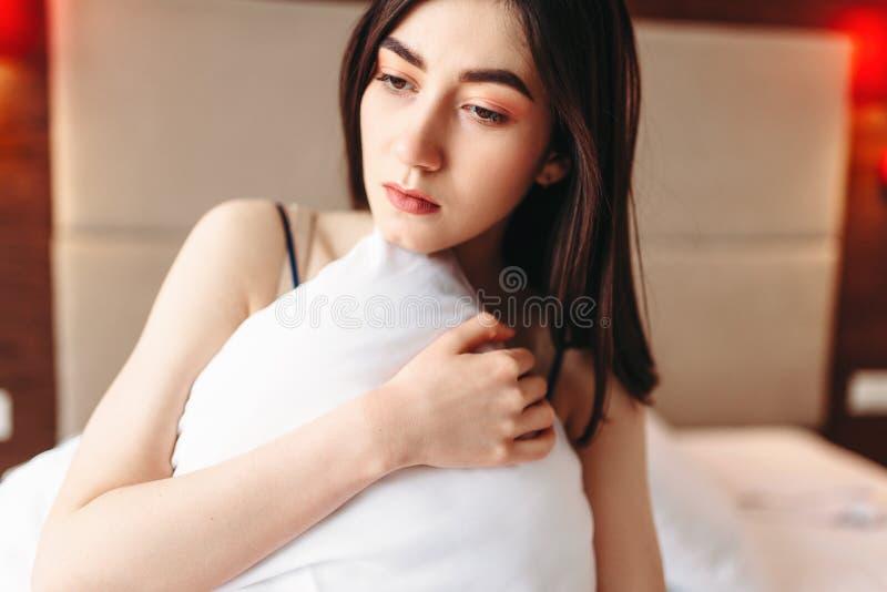 La donna nella depressione si siede a letto sotto la coperta fotografie stock libere da diritti