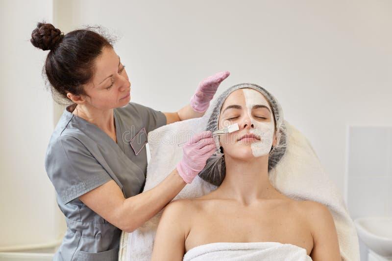 La donna nella maschera sul fronte nel salone della stazione termale, cosmetologo applica l'agente cosmetico con la spazzola spec fotografia stock libera da diritti