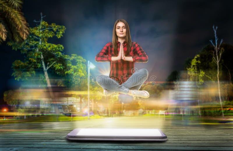 La donna nella posa di yoga si libra sopra un grande telefono immagine stock libera da diritti