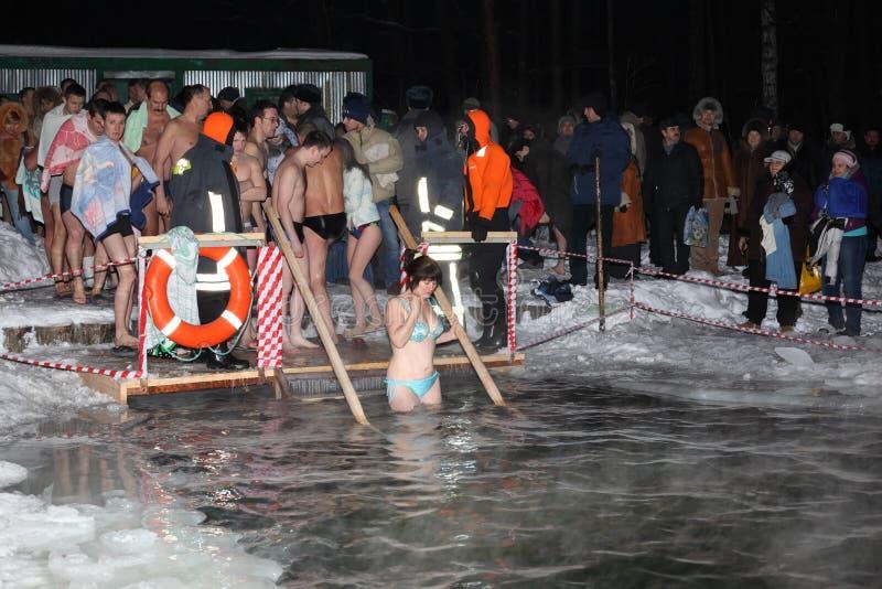 La donna non definita discende nell'acqua per il battesimo fotografie stock libere da diritti