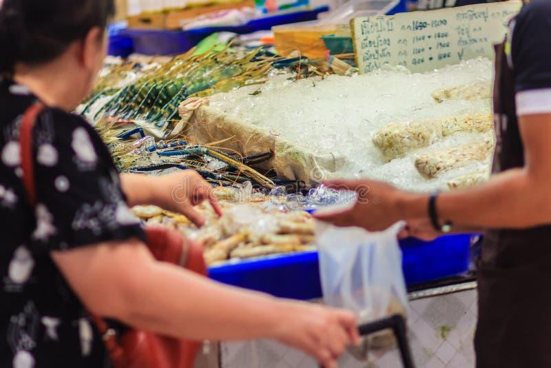 La donna non identificata al mercato dei frutti di mare sta comprando il lar extra fotografia stock libera da diritti