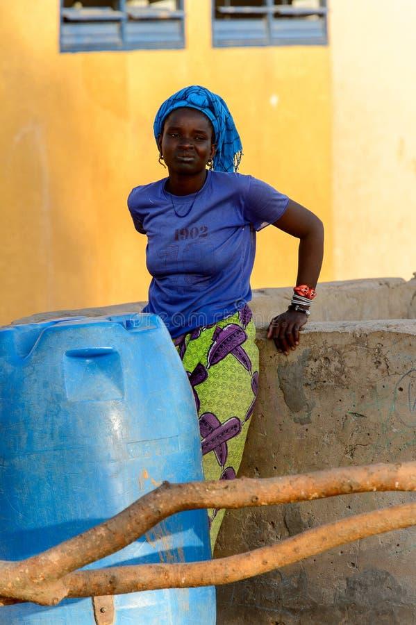 La donna non identificata di Fulani in foulard si appoggia il acqua tiraggio immagine stock libera da diritti