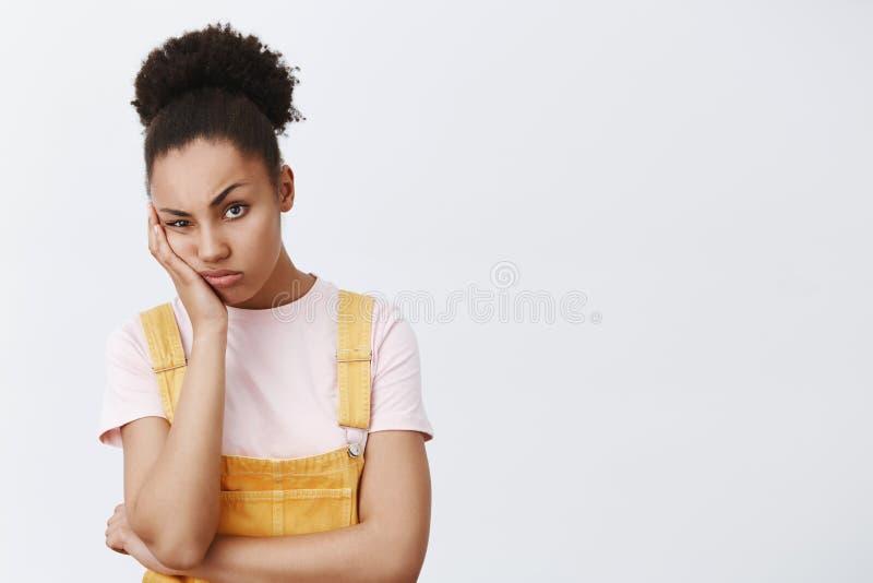 La donna odia quando amico che protesta sulla sua vita, fissando con l'espressione indifferente e annoiata, appoggiantesi la palm fotografia stock libera da diritti
