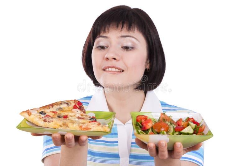 La donna opera la scelta di pizza e di insalata sana immagini stock libere da diritti
