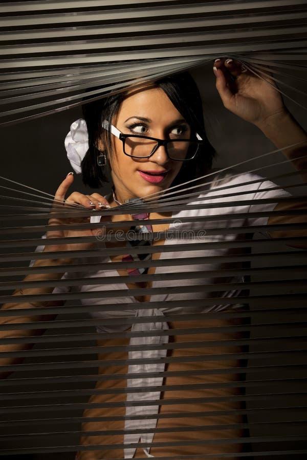 La donna osserva il pigolio alla gelosia immagine stock