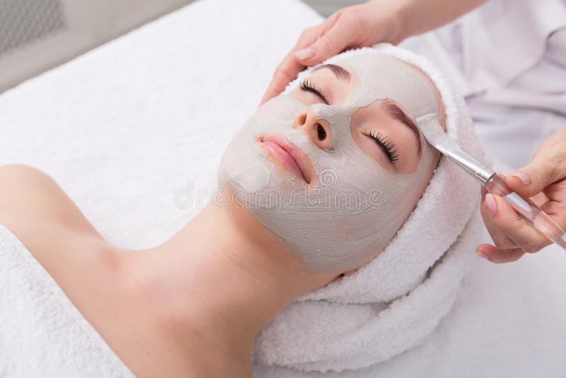 La donna ottiene la maschera di protezione dall'estetista alla stazione termale fotografia stock