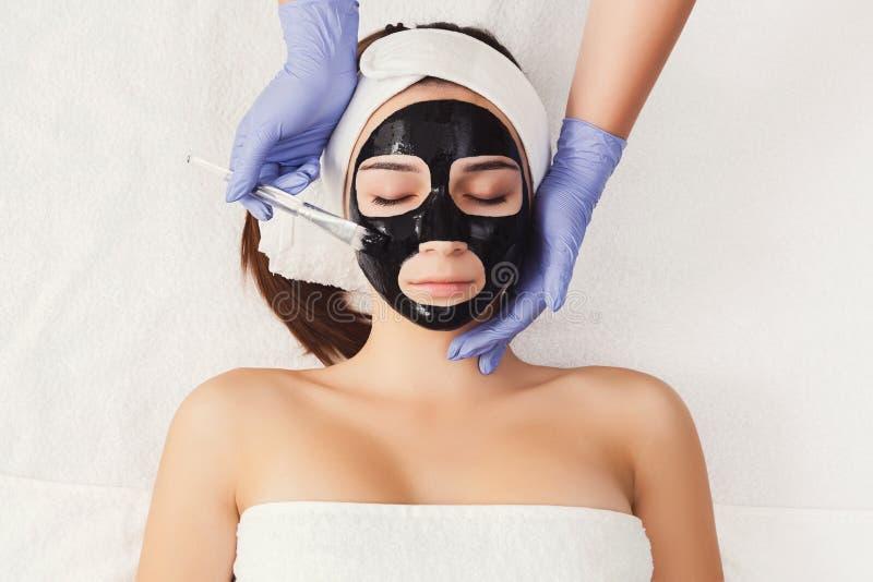 La donna ottiene la maschera di protezione dall'estetista alla stazione termale fotografie stock