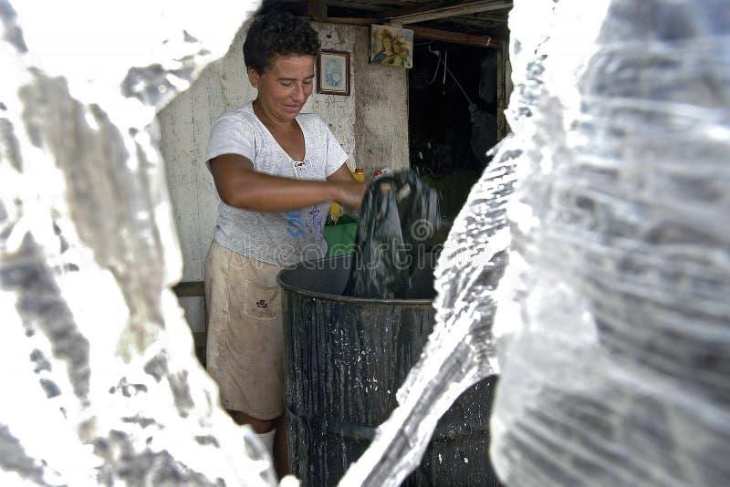 La donna paraguaiana lava la plastica per riciclare fotografia stock libera da diritti