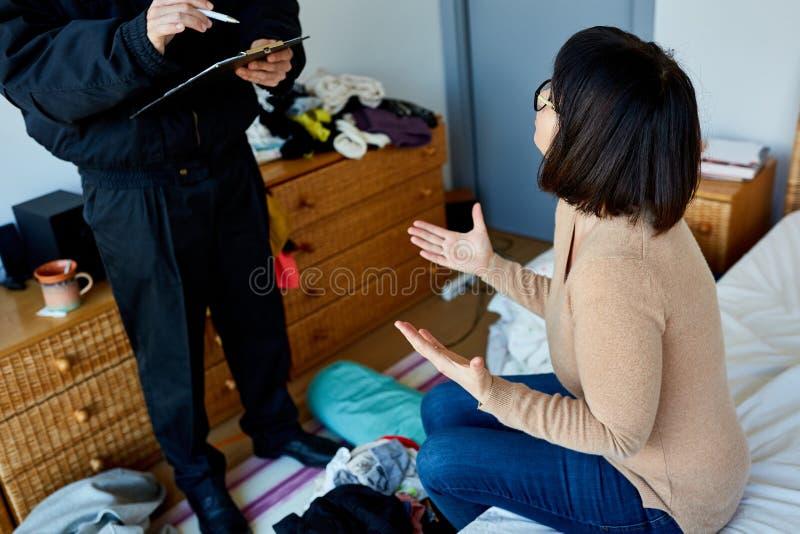 La donna parla del furto con scasso con l'ufficiale di polizia immagini stock