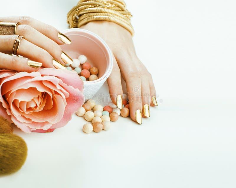 La donna passa con il manicure dorato molti anelli che tengono le spazzole, roba del truccatore alla moda e pura immagine stock