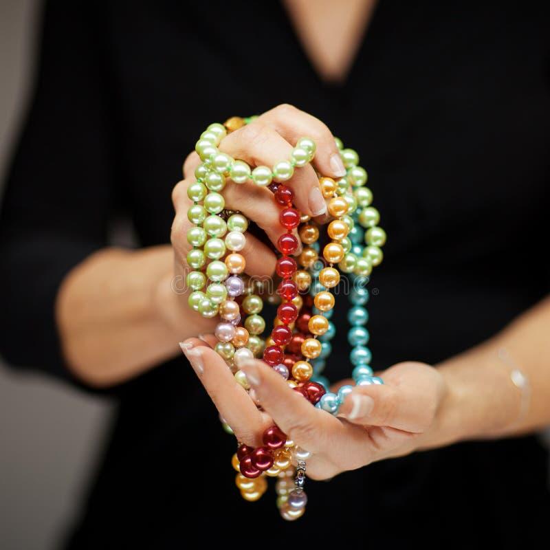 La donna passa i gioielli della perla della tenuta, colpo sensuale dello studio fotografia stock libera da diritti