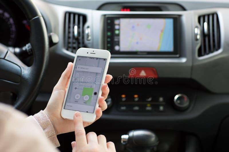 La donna passa il iPhone 6S della tenuta con il taxi Uber dell'applicazione fotografie stock libere da diritti