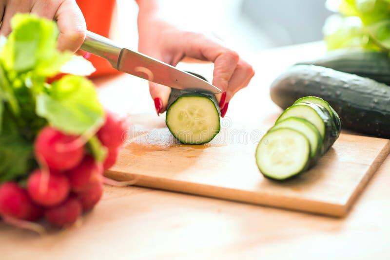 La donna passa il taglio del veg fresco con il coltello sul tagliere immagine stock libera da diritti