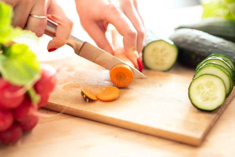 La donna passa il taglio del veg fresco con il coltello sul tagliere fotografia stock libera da diritti