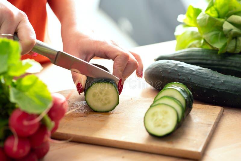 La donna passa il taglio del veg fresco con il coltello sul tagliere fotografie stock libere da diritti