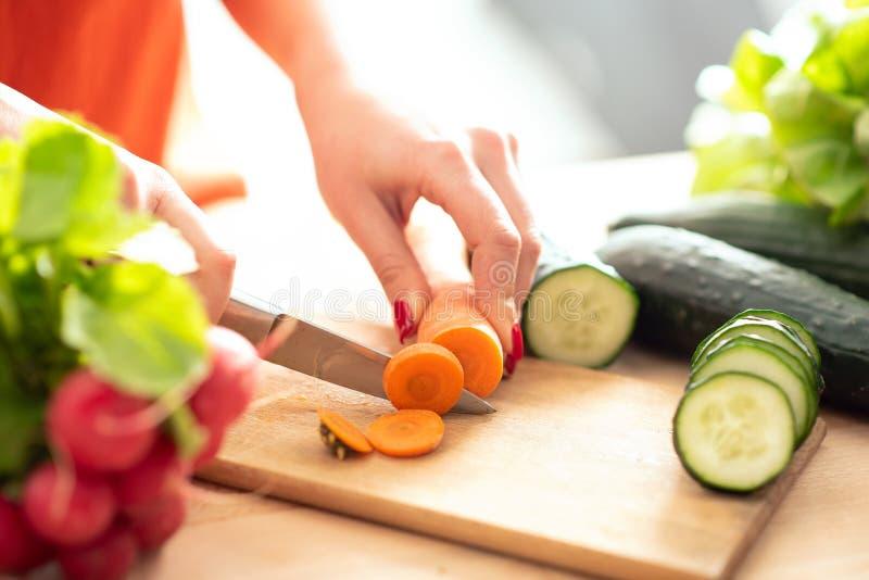 La donna passa il taglio del veg fresco con il coltello sul tagliere immagini stock libere da diritti