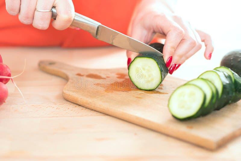 La donna passa il taglio del veg fresco con il coltello sul tagliere fotografie stock