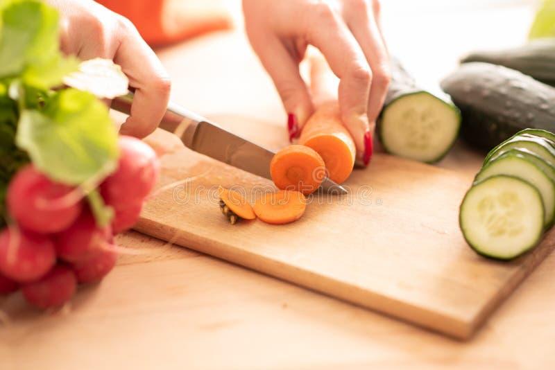 La donna passa il taglio del veg fresco con il coltello sul tagliere immagine stock