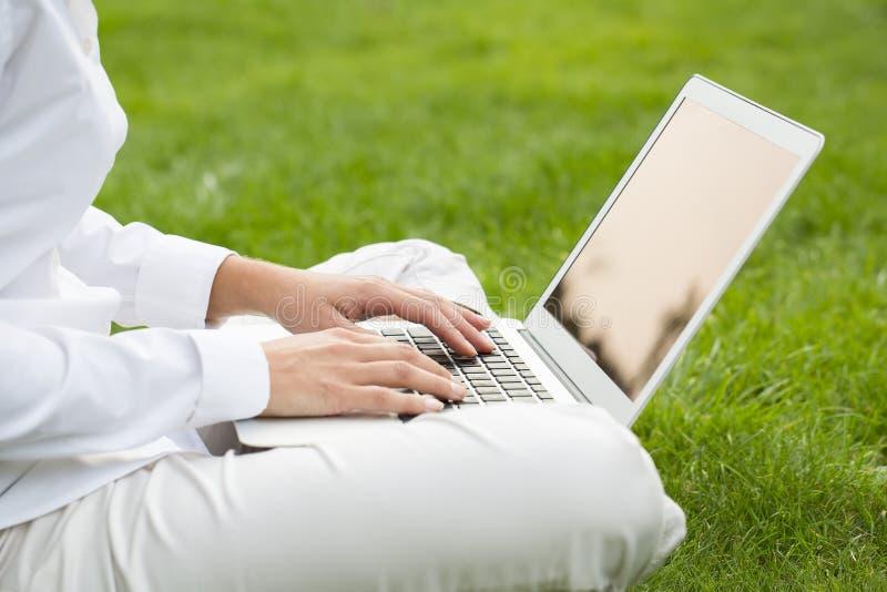 La donna passa la battitura a macchina su una tastiera del computer portatile, in giardino fotografia stock