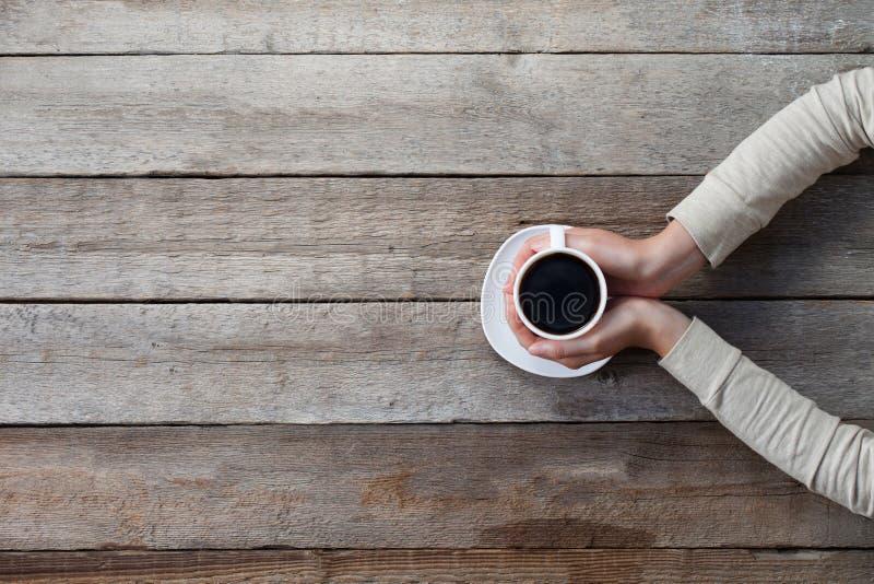 La donna passa la tazza della tenuta della tazza calda del coffe immagini stock