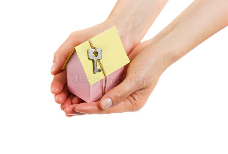 La donna passa la tenuta del modello della casa del cartone con la chiave su cordicella isolata su fondo bianco fotografie stock