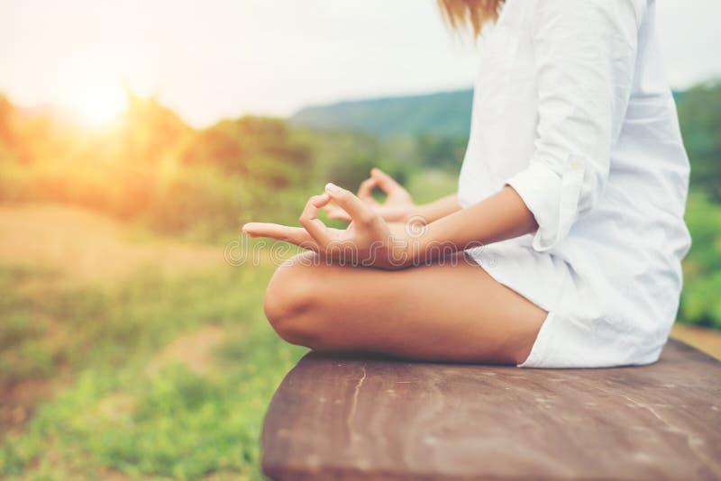 La donna passa le meditazioni di yoga e la fabbricazione del simbolo di zen con il suo ha fotografia stock