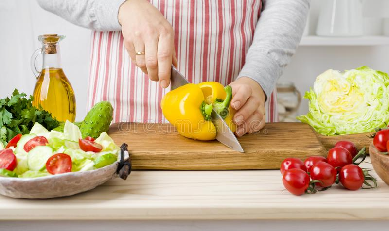 La donna passa le verdure di taglio a bordo in cucina che cucina l'insalata fotografia stock libera da diritti