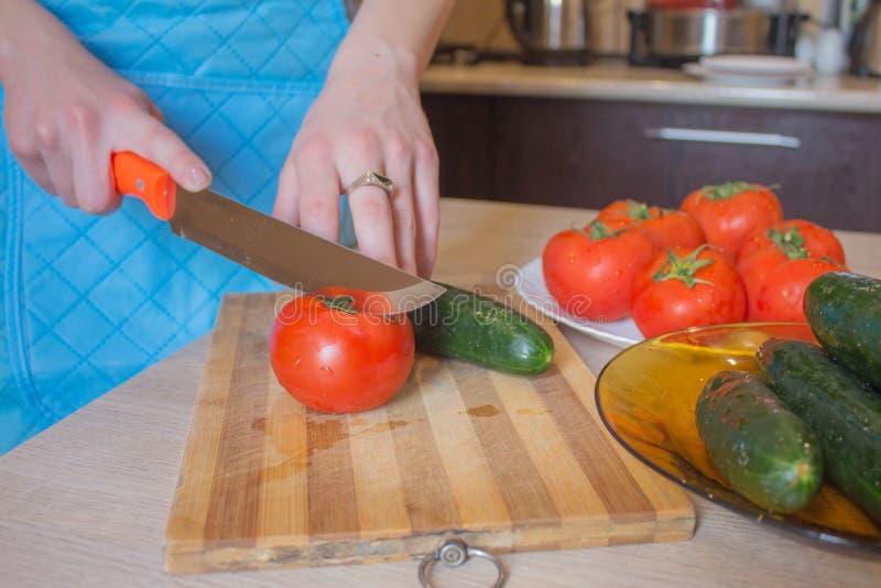La donna passa le verdure di taglio sulla lavagna della cucina Alimento sano Donna che prepara le verdure, cucinanti pasto sano i fotografia stock libera da diritti