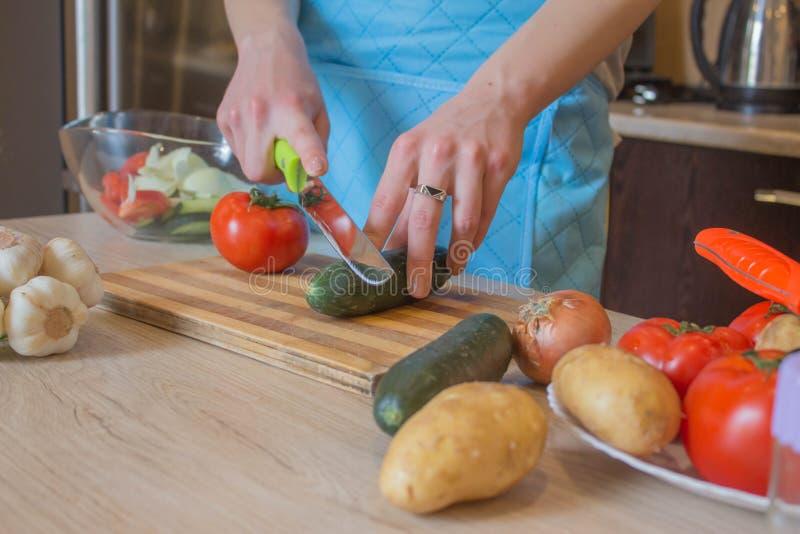 La donna passa le verdure di taglio sulla lavagna della cucina Alimento sano Donna che prepara le verdure, cucinanti pasto sano i fotografie stock