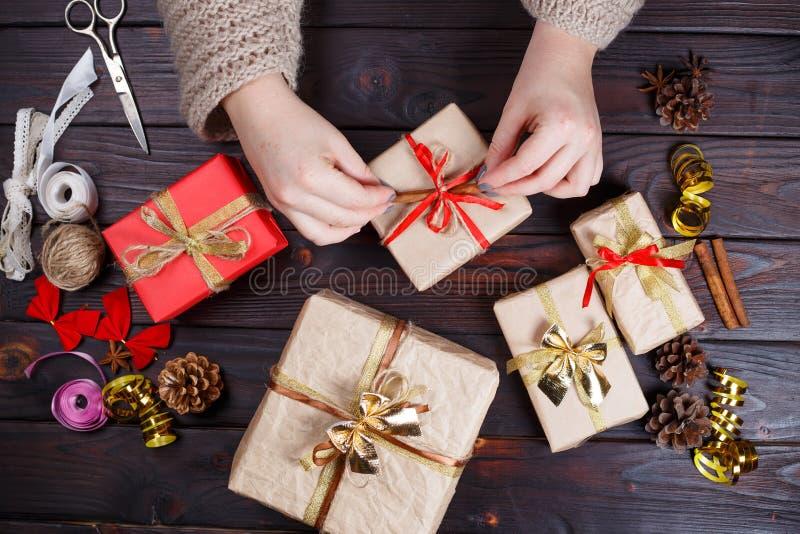 La donna passa lo spostamento del presente fatto a mano di festa di Natale nel mestiere fotografie stock libere da diritti