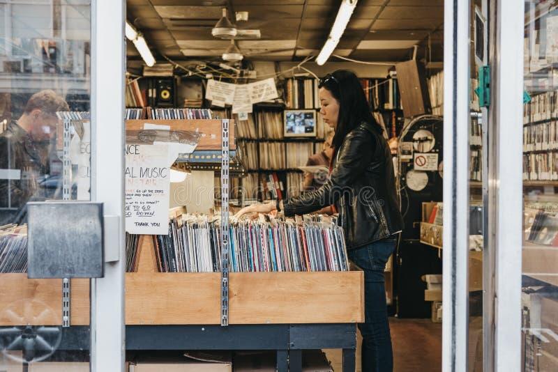 La donna passa in rassegna le annotazioni di vinile ad un deposito in Notting Hill, Londra immagine stock libera da diritti